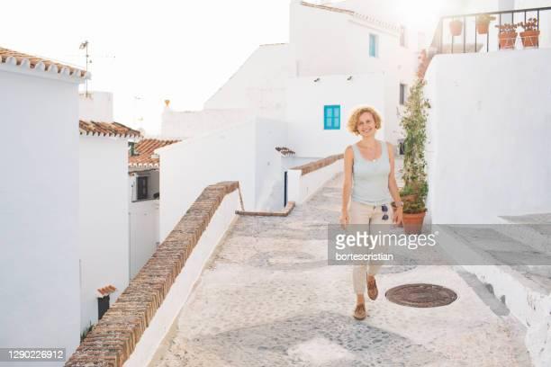 portrait of young woman standing against building - bortes fotografías e imágenes de stock