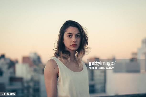 portrait of young woman standing against clear sky in city during sunset - foco diferencial imagens e fotografias de stock
