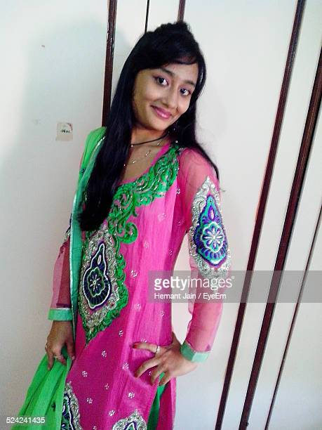 portrait of young woman standing against closet - salwar kameez stock photos and pictures