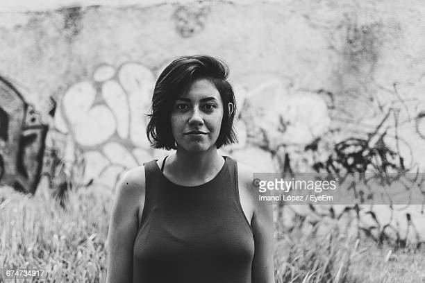 portrait of young woman standing against graffiti wall - mexico black and white stock pictures, royalty-free photos & images