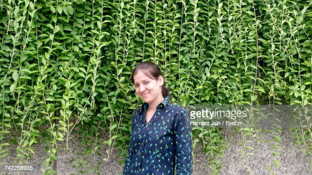 portrait of young woman standing against plants - adults only stock pictures, royalty-free photos & images