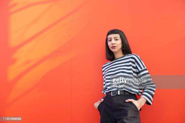 portrait of young woman standing against red background. - secteur de la mode photos et images de collection