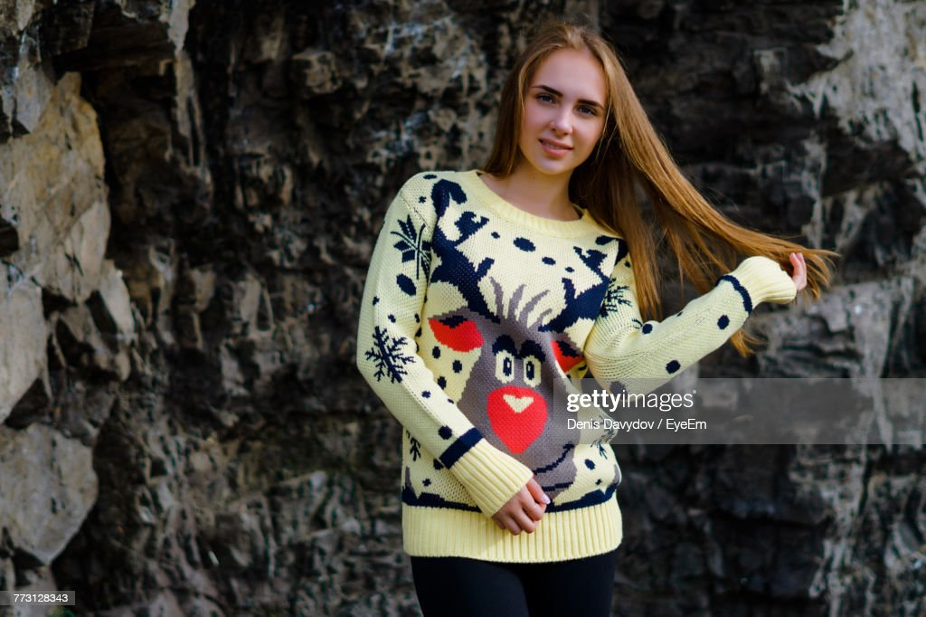 Portrait Of Young Woman Standing Against Rock : Photo
