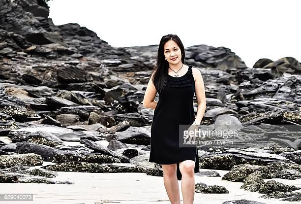 Portrait Of Young Woman Standing Against Rocks At Beach