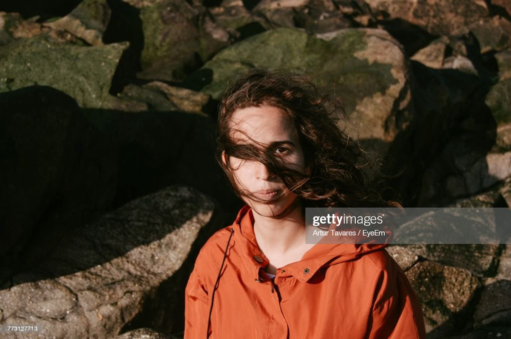 Portrait Of Young Woman Standing Against Rocks : Photo