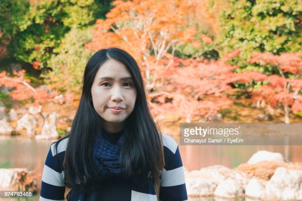 portrait of young woman standing against trees - chanayut stock photos and pictures