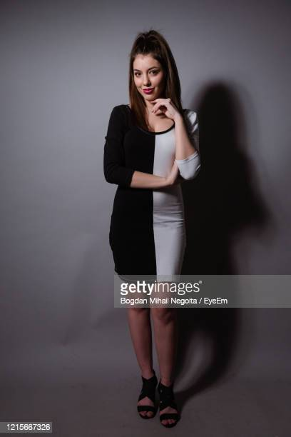portrait of young woman standing against wall - bogdan negoita stock pictures, royalty-free photos & images