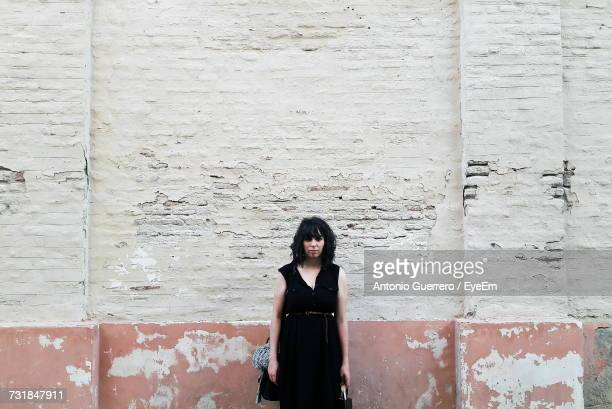 portrait of young woman standing against wall - deterioration stock pictures, royalty-free photos & images