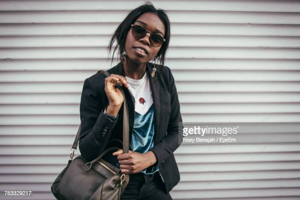 portrait of young woman standing against wall - metallic purse stock pictures, royalty-free photos & images