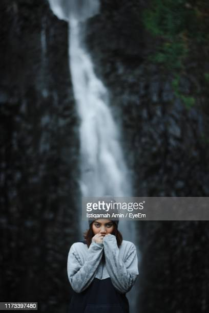 portrait of young woman standing against waterfall - makassar stock pictures, royalty-free photos & images