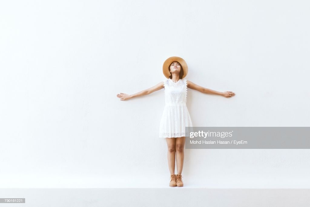 Portrait Of Young Woman Standing Against White Background : Stock Photo