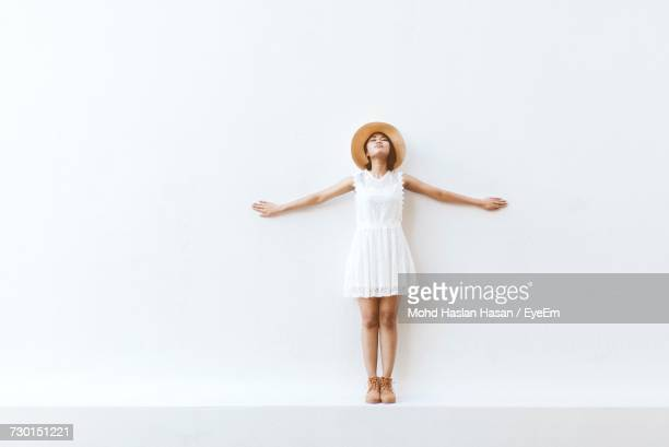 portrait of young woman standing against white background - arms outstretched stock pictures, royalty-free photos & images