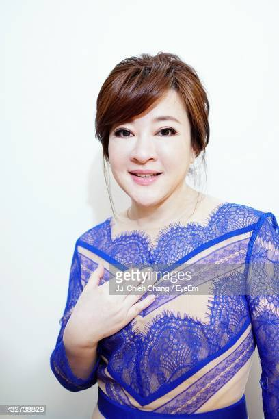 portrait of young woman standing against white background - chang jui chieh stock photos and pictures