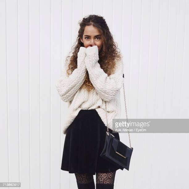 portrait of young woman standing against white wall - ankle length stock pictures, royalty-free photos & images