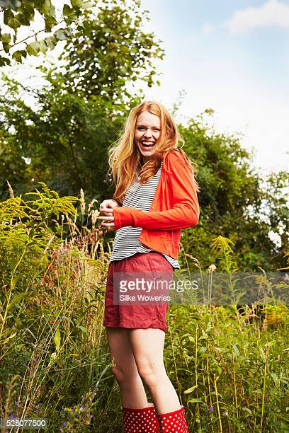 Portrait of young woman standing among wild flowers and laughing