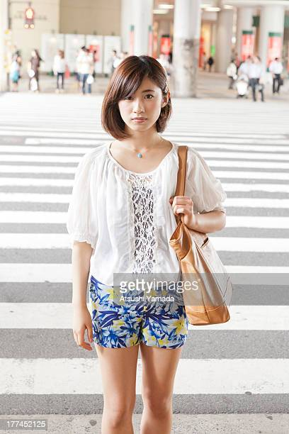 Portrait of young woman standing at crosswalk