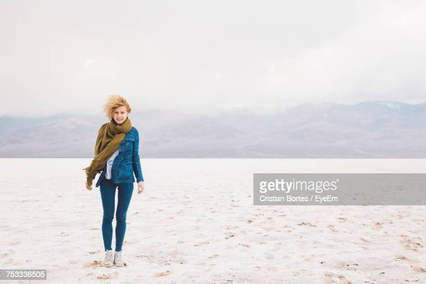 Portrait Of Young Woman Standing At Death Valley National Park Against Cloudy Sky