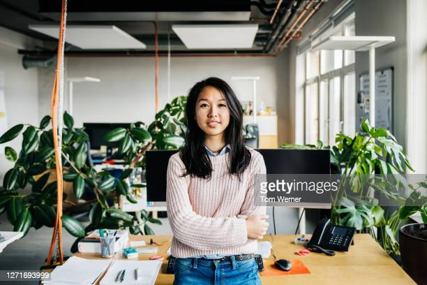 portrait of young woman standing at her desk - young women stock pictures, royalty-free photos & images