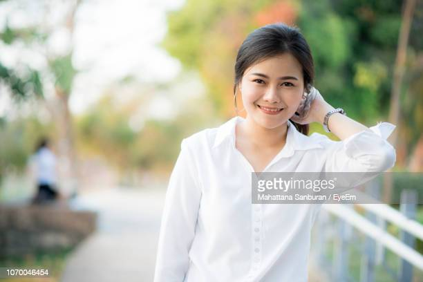 portrait of young woman standing at park - シャツ ストックフォトと画像