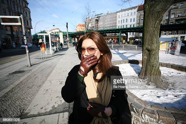 Portrait Of Young Woman Standing At Sidewalk Covering Mouth With Hand
