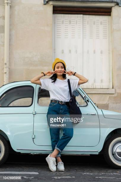 portrait of young woman standing at small car - french women stock-fotos und bilder