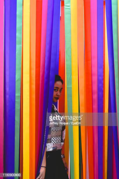 portrait of young woman standing by colorful hanging ribbons - jeffrey roque stock photos and pictures