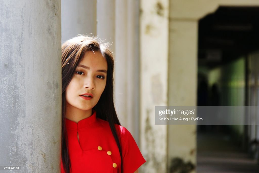 Portrait Of Young Woman Standing By Column : Stock Photo