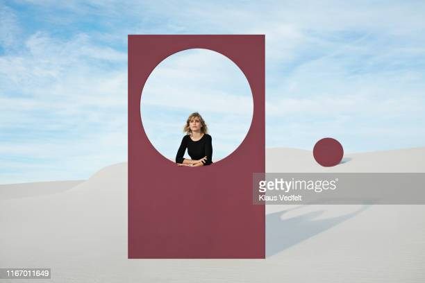 portrait of young woman standing by maroon portal at desert - circle stock pictures, royalty-free photos & images