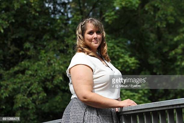 portrait of young woman standing by railing against trees - fat blonde women stock photos and pictures