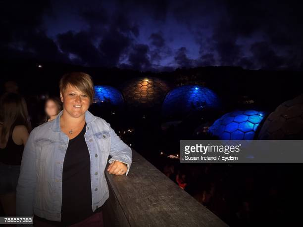 Portrait Of Young Woman Standing By Railing At Eden Project During Night