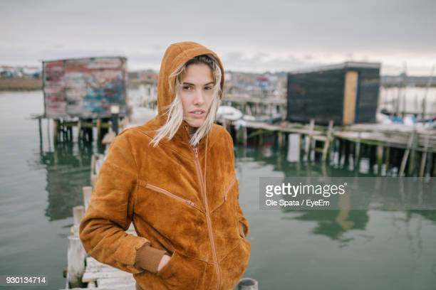 portrait of young woman standing by river against sky - hands in pockets stock photos and pictures