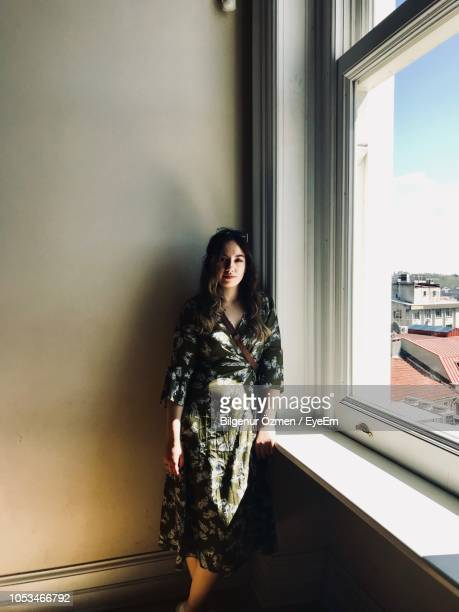 portrait of young woman standing by window at home - one young woman only stock pictures, royalty-free photos & images
