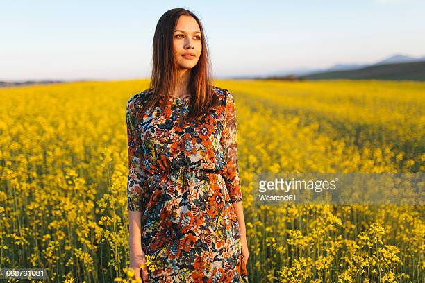 Portrait of young woman standing in a rape field