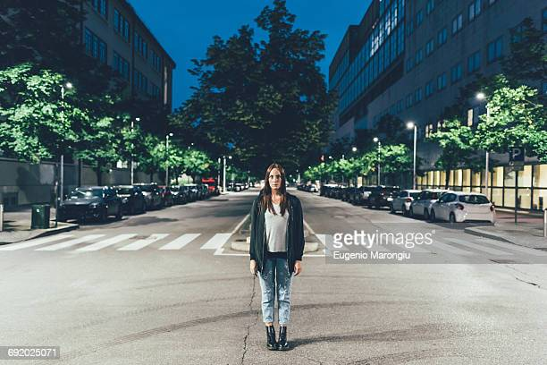 Portrait of young woman standing in centre of city road at night