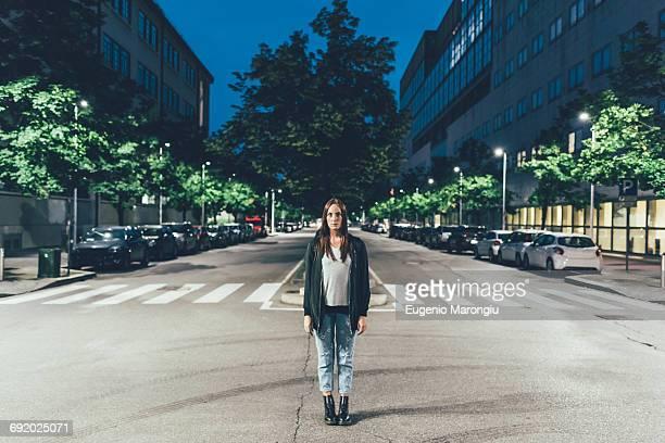 portrait of young woman standing in centre of city road at night - al centro foto e immagini stock
