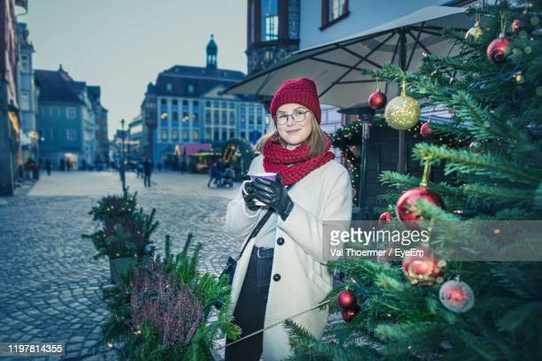 portrait of young woman standing in city - val thoermer stock-fotos und bilder
