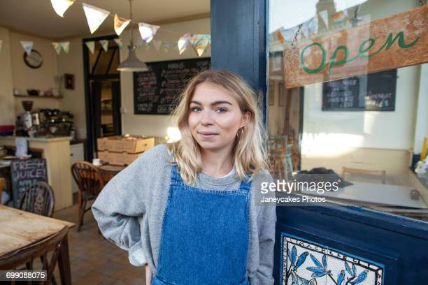 Portrait of young woman standing in doorway of cafe