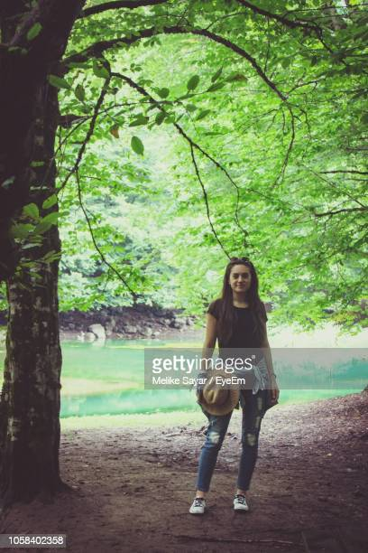 portrait of young woman standing in forest - melike stock pictures, royalty-free photos & images