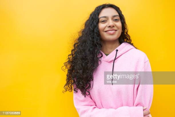 portrait of young woman standing in front of a yellow background - sweatshirt stock pictures, royalty-free photos & images