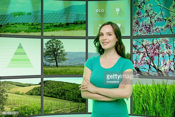 Portrait of young woman standing in front of graphical screens, displaying environmental images