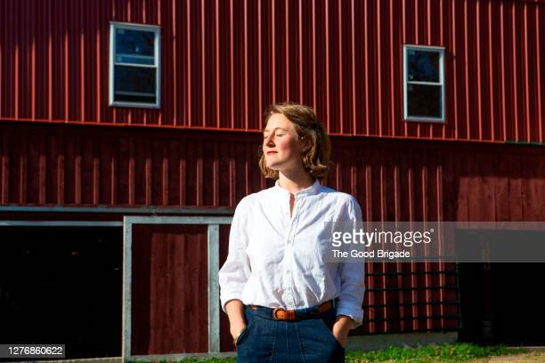 portrait of young woman standing in front of red barn - hands in pockets stock pictures, royalty-free photos & images