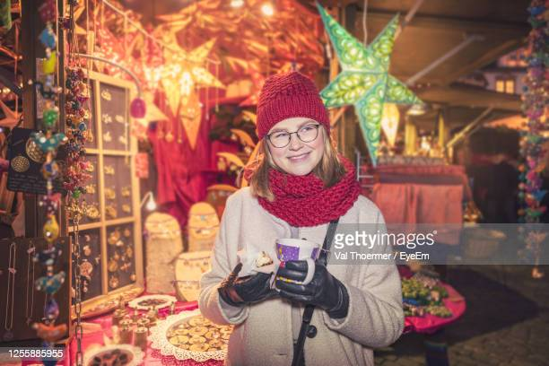 portrait of young woman standing in illuminated christmas tree during winter - val thoermer stock-fotos und bilder