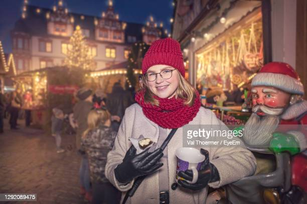 portrait of young woman standing in market during christmas - val thoermer stock-fotos und bilder