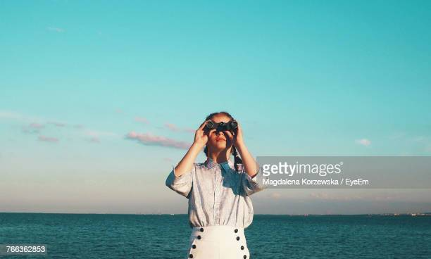 portrait of young woman standing in sea against sky - guardare in una direzione foto e immagini stock