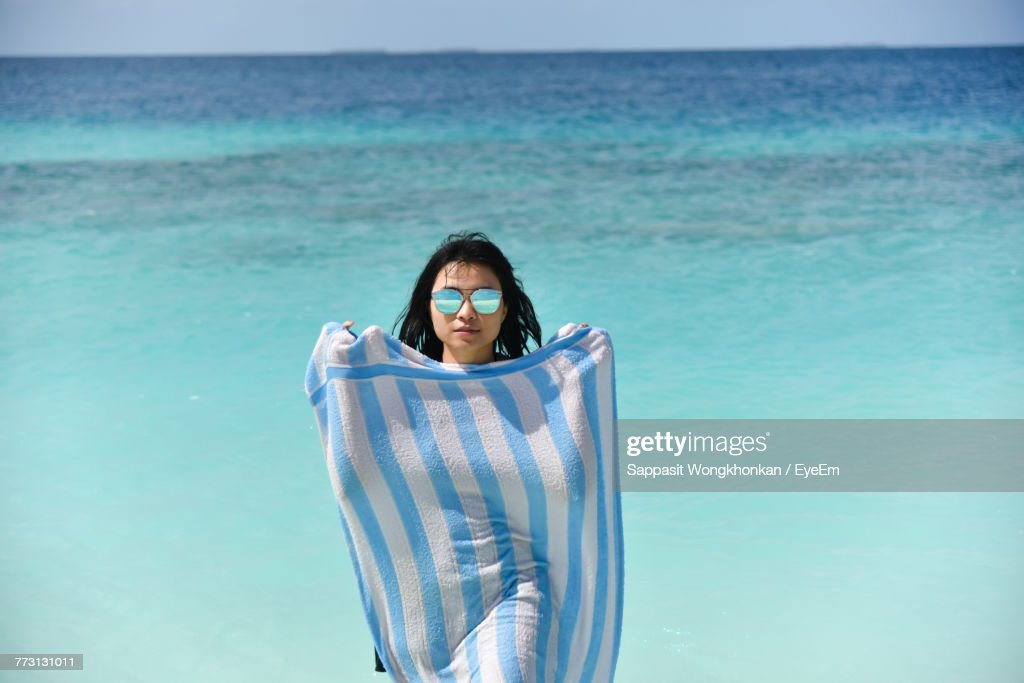 Portrait Of Young Woman Standing In Sea Against Sky : Photo