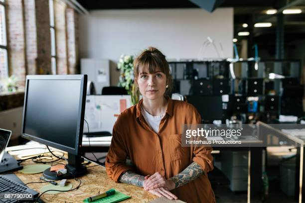 Portrait of young woman standing in startup business space