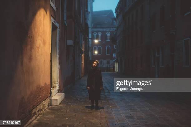 portrait of young woman standing in street at dusk, venice, italy - endast en ung kvinna bildbanksfoton och bilder