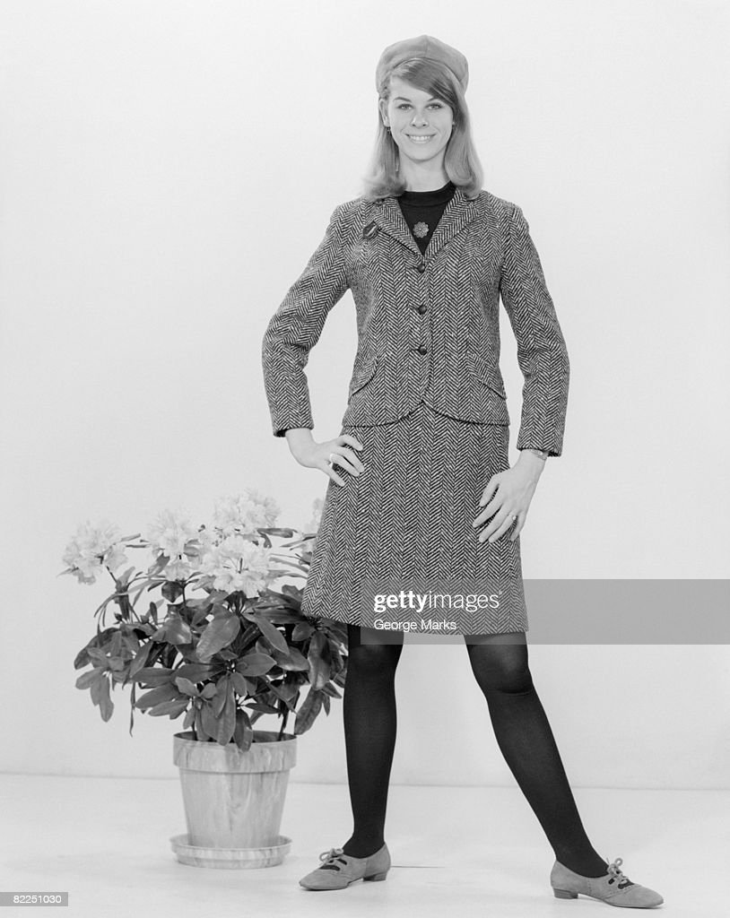 Portrait of young woman standing next to potted plant : Stock Photo
