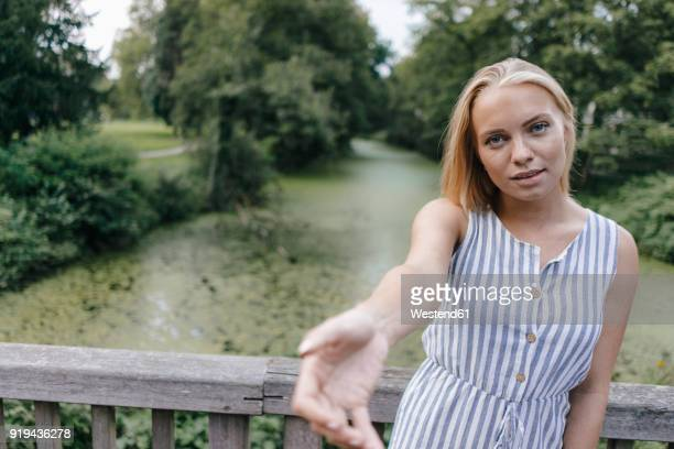 portrait of young woman standing on a bridge reaching out her hand - greifen stock-fotos und bilder
