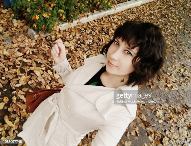 portrait of young woman standing on autumn leaves covered footpath - coat ストックフォトと画像